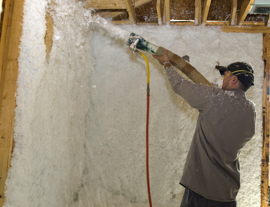 contractor blowing insulation on wall